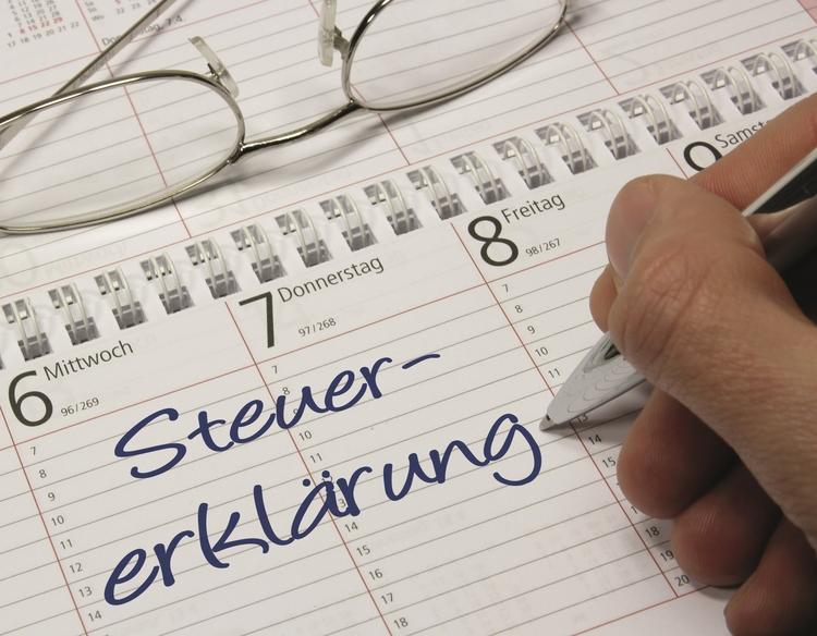 Kalender mit Hand die Steuererklärung schreibt